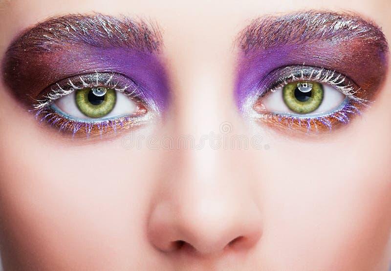 Żeńska twarz z zielonym pistacjowym colour ono przygląda się, evening fiołkowego pur fotografia royalty free