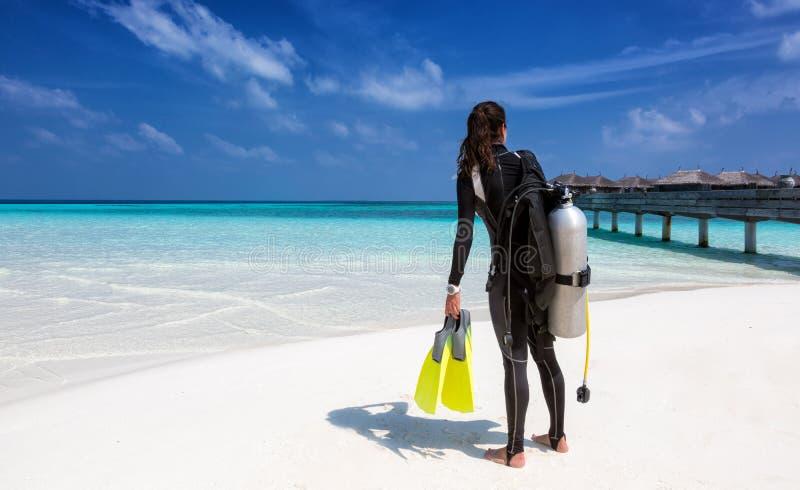 Żeński akwalungu nurek z nurkowym wyposażeniem na plaży obrazy stock
