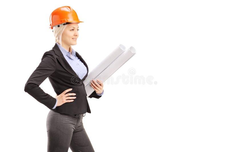 Żeński architekt jest ubranym pomarańczowego hełm i trzyma bluepr fotografia stock