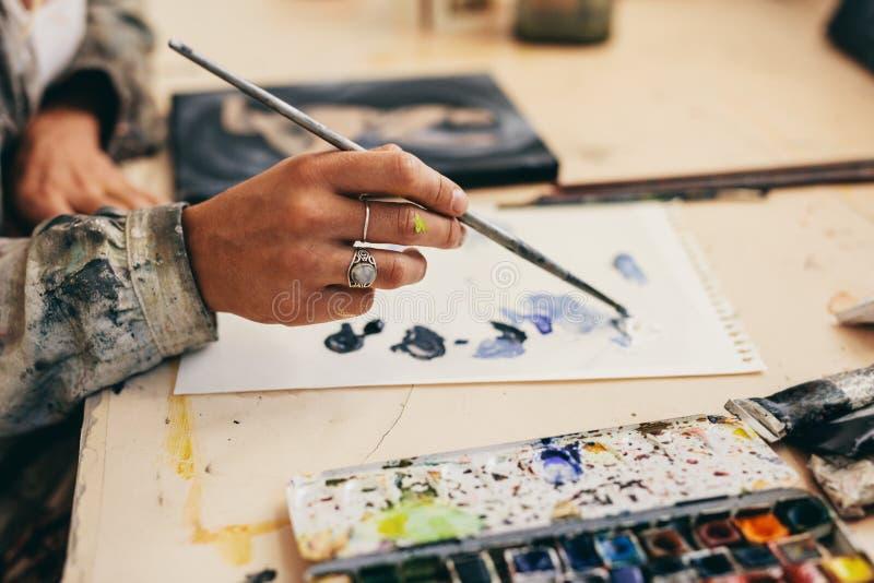 Żeński artist& x27; s ręka miesza kolory na papierze obrazy stock