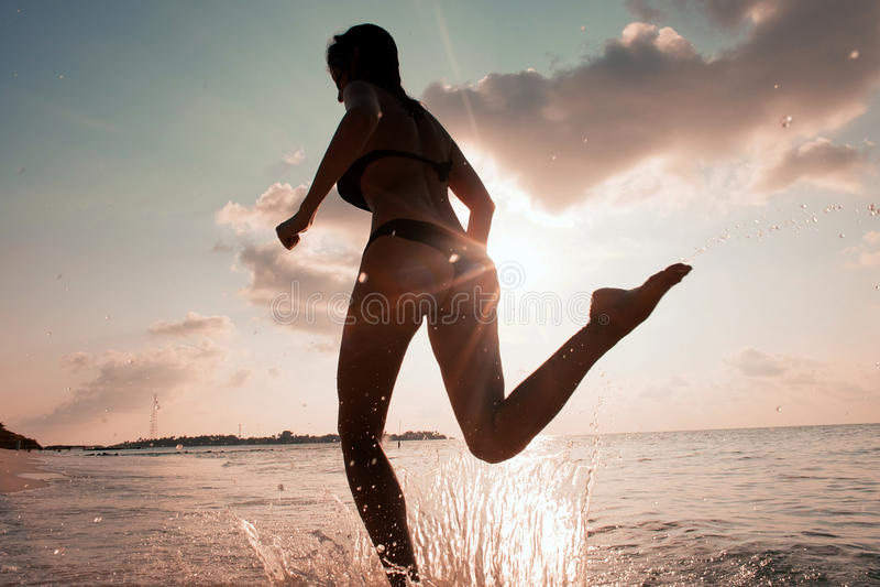Żeński biegacz na plaży przy zmierzch sylwetką w lotniczy dalekim zdjęcie royalty free