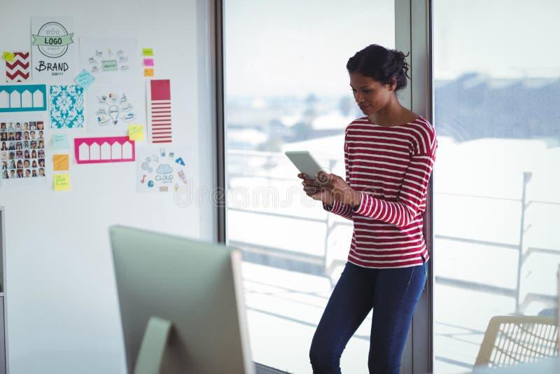 Żeński bizneswoman używa cyfrową pastylkę w biurze podczas gdy opierający na okno fotografia stock