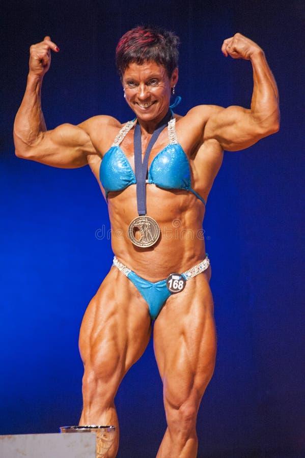 Żeński bodybuilder przedstawia jej budowę ciała napina jej mięśnie zdjęcie royalty free