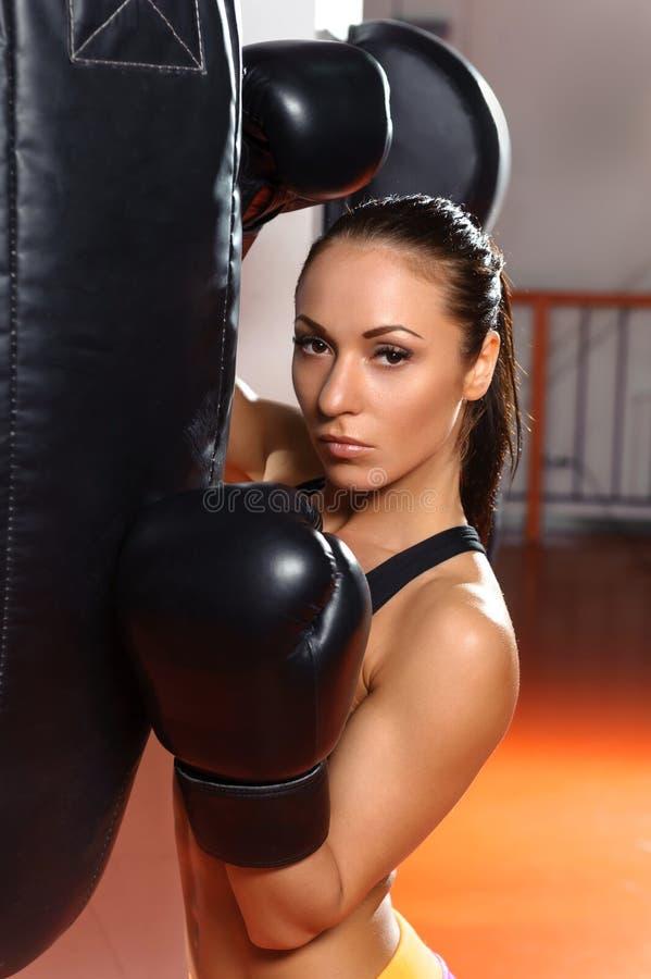 Żeński bokser z uderzać pięścią torbę zdjęcie royalty free