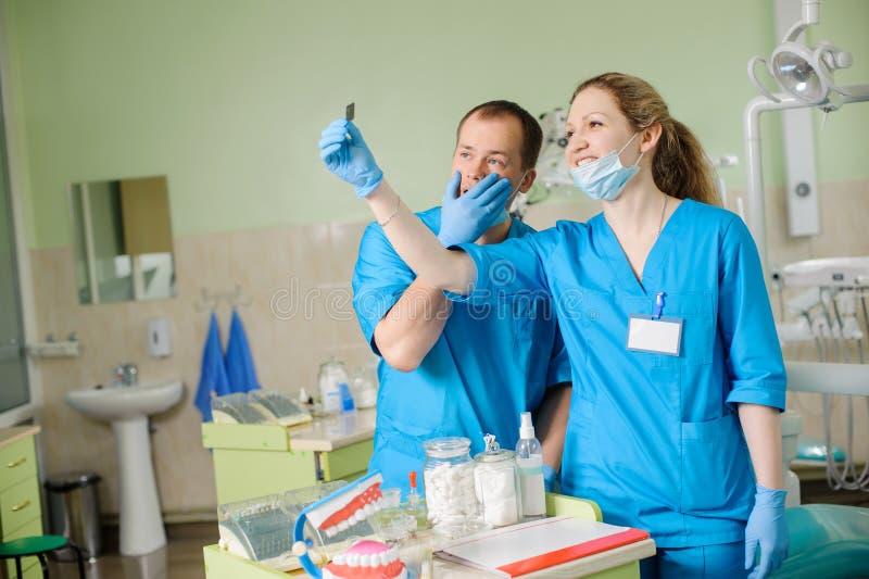 Żeński dentysta pokazuje promieniowanie rentgenowskie męski kolega przy stomatologiczną kliniką fotografia royalty free