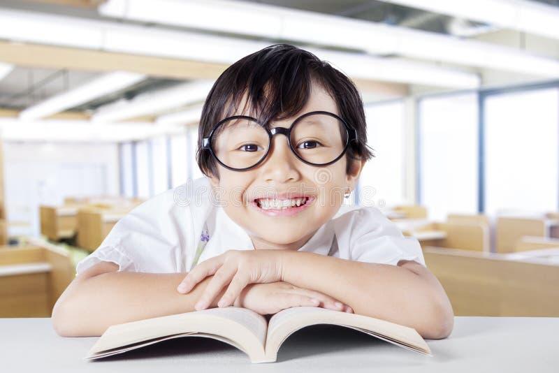 Żeński dzieciak ono uśmiecha się przy kamerą podczas gdy czytelnicza książka fotografia stock