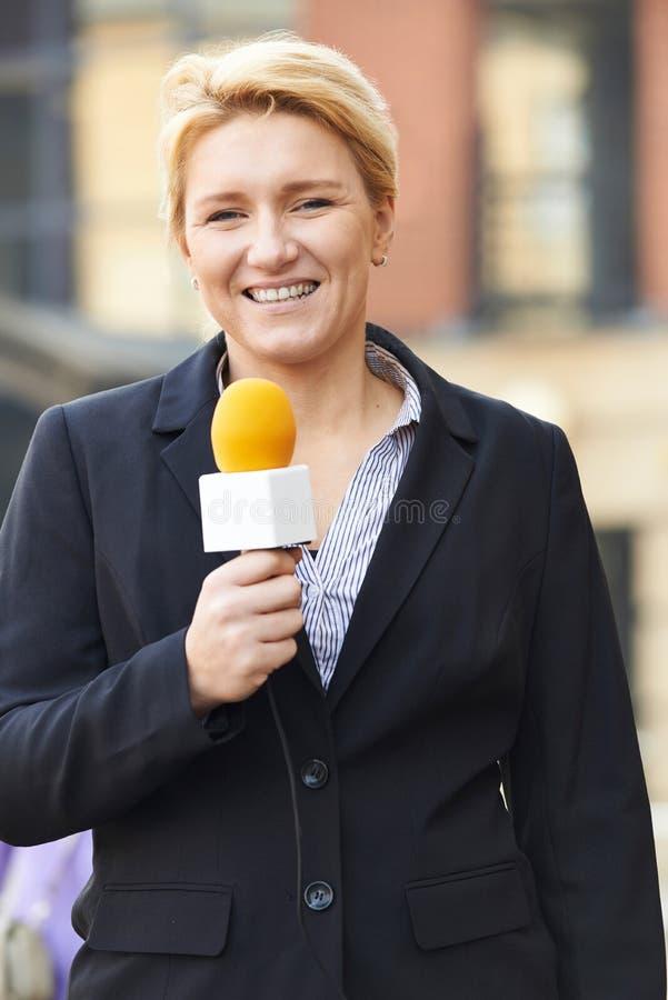 Żeński dziennikarza transmitowanie Na zewnątrz budynku biurowego zdjęcia stock