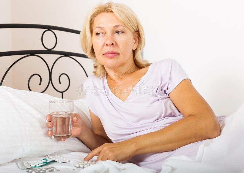Żeński emeryt bierze medycynę zdjęcia stock