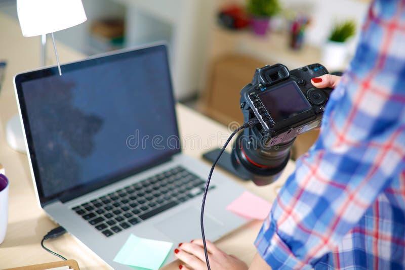 Żeński fotografa obsiadanie na biurku z obraz royalty free