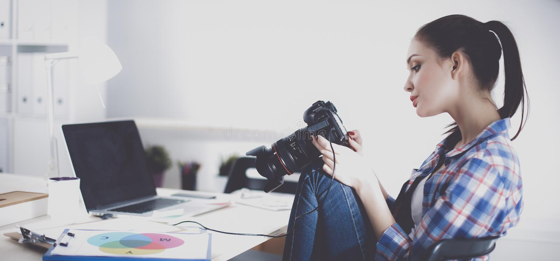 Żeński fotografa obsiadanie na biurku z laptopem fotografia stock