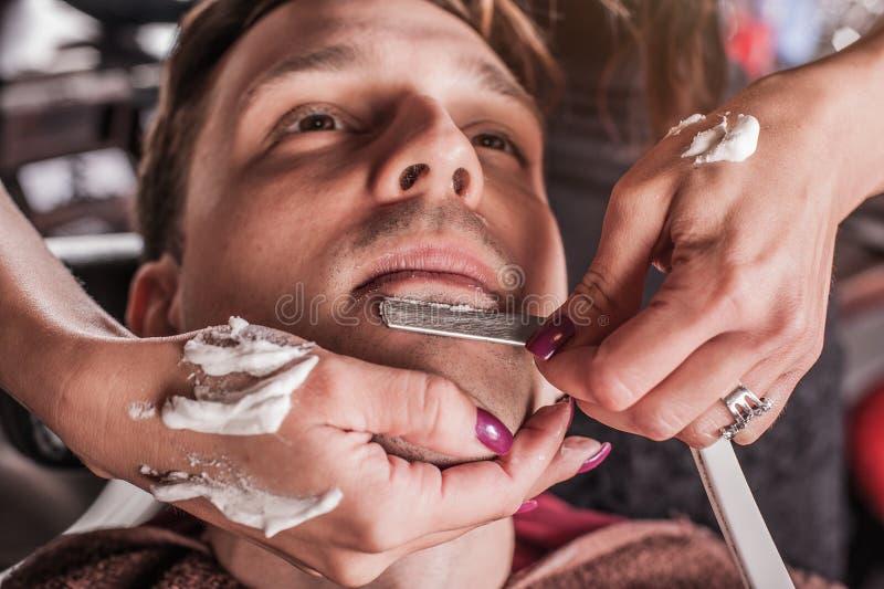 Żeński fryzjer męski goli klienta zdjęcia royalty free