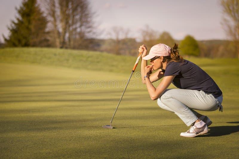 Żeński golfowego gracza kucanie na zieleni obraz royalty free