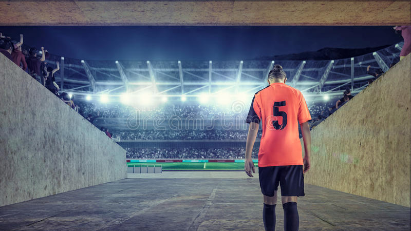 Żeński gracz piłki nożnej wchodzić do pole na zatłoczonym stadium zdjęcie royalty free