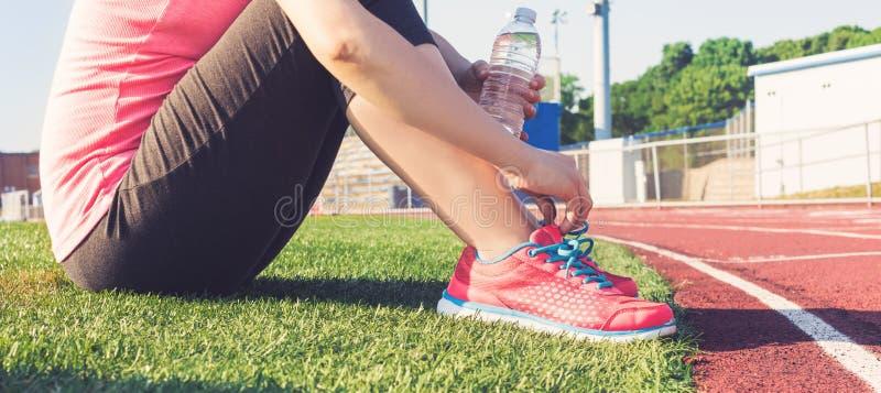 Żeński jogger obsiadanie na stronie stadium ślad fotografia stock