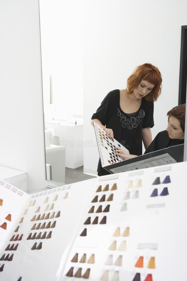 Żeński klient I fryzjer Patrzeje kolor mapę obrazy royalty free