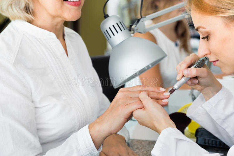 Żeński klient robi gwoździom w gwoździa salonie w zakończeniu zdjęcia royalty free