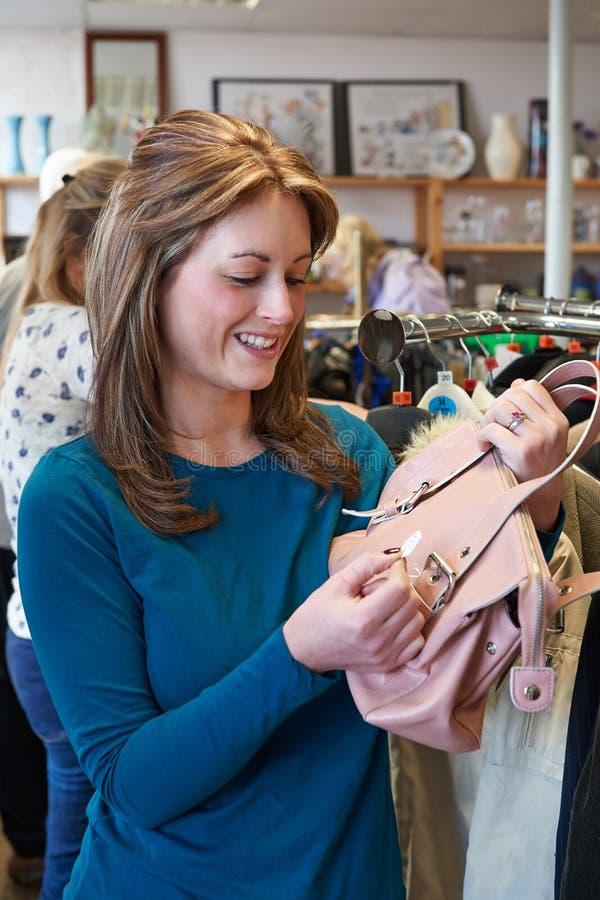 Żeński kupujący Patrzeje torebkę W oszczędzanie sklepie obraz royalty free