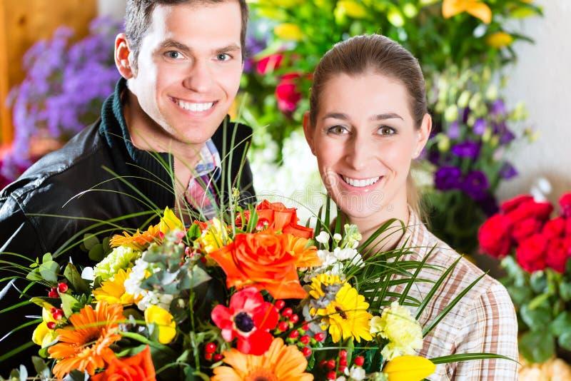 Żeński kwiaciarni i samiec klient w kwiatu sklepie zdjęcia royalty free