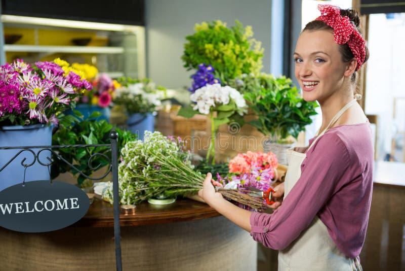 Żeński kwiaciarni narządzania kwiatu bukiet w kwiatu sklepie zdjęcie stock