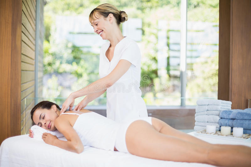 Żeński masażysta masuje pięknej kobiety przy zdrojem zdjęcia stock