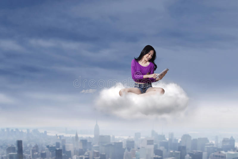 Żeński nastoletni z pastylką na chmurze obraz stock
