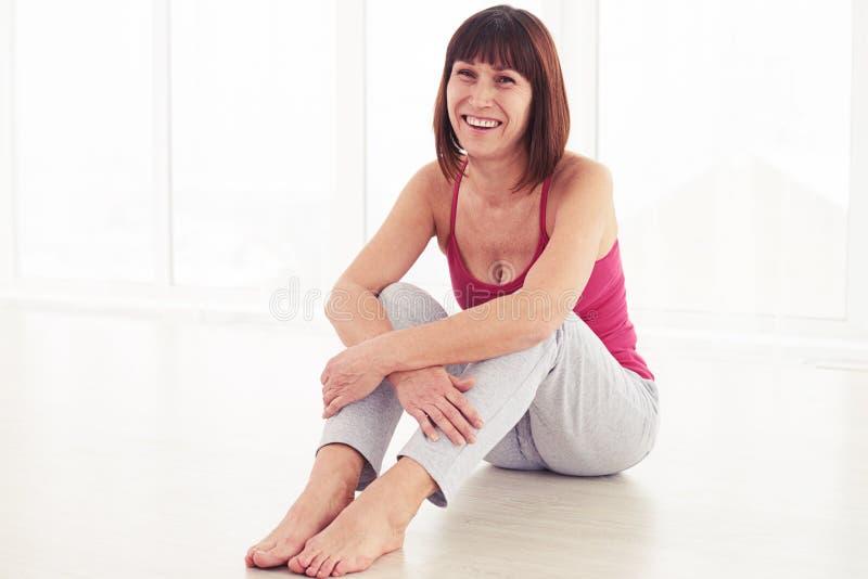 Żeński obsiadanie na joga macie obejmowanie nogach i zdjęcia royalty free