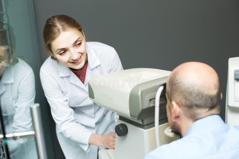 Żeński oftalmolog i dojrzały pacjent sprawdza wzrok w c zdjęcia stock