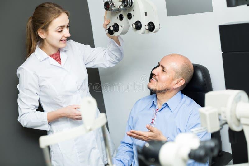 Żeński oftalmolog i dojrzały pacjent sprawdza wzrok w c zdjęcie royalty free