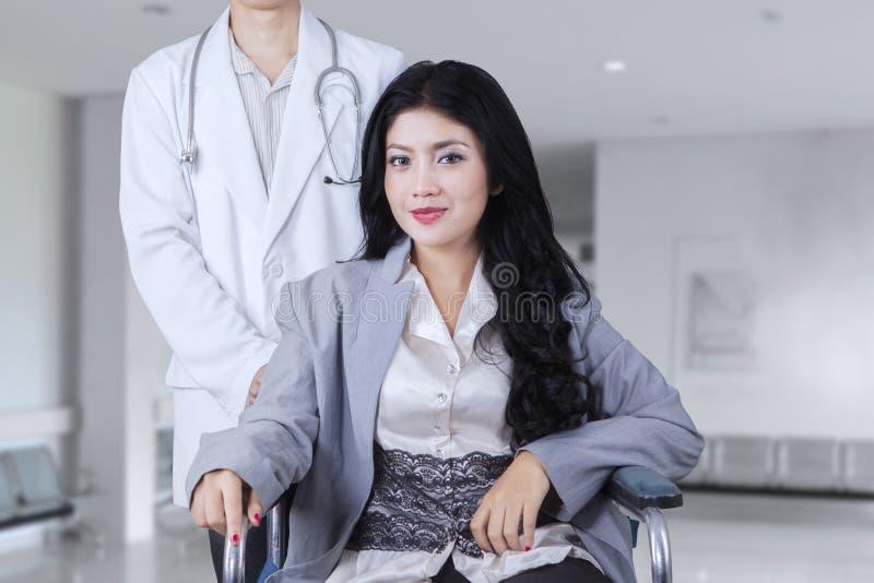 Żeński pacjent siedzi na wózku inwalidzkim w korytarzu zdjęcia stock