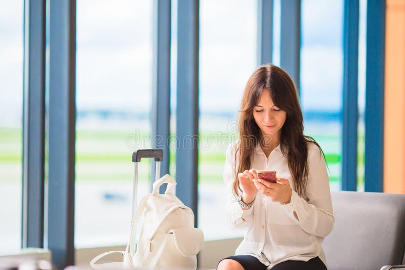 Żeński pasażer w lotniskowym holu czekaniu dla lota samolotu Sylwetka kobieta z telefonem komórkowym w lotnisku iść fotografia royalty free