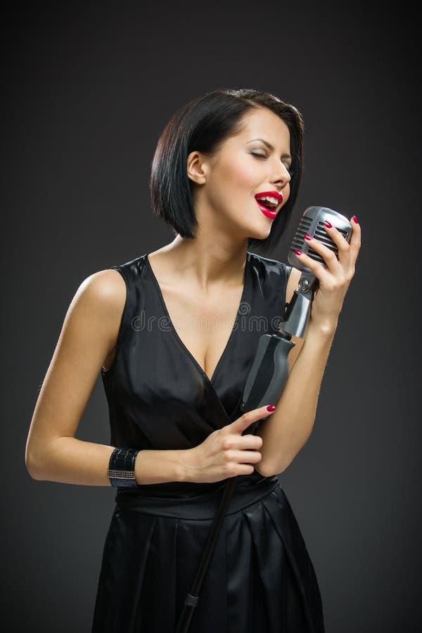 Żeński piosenkarz utrzymuje mic z zamkniętymi oczami obrazy royalty free
