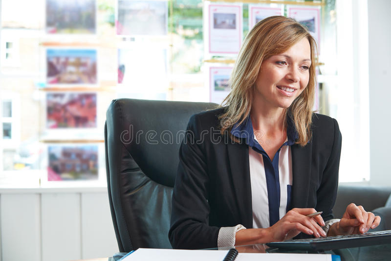 Żeński pośrednik w handlu nieruchomościami Pracuje Przy komputerem W biurze zdjęcia stock
