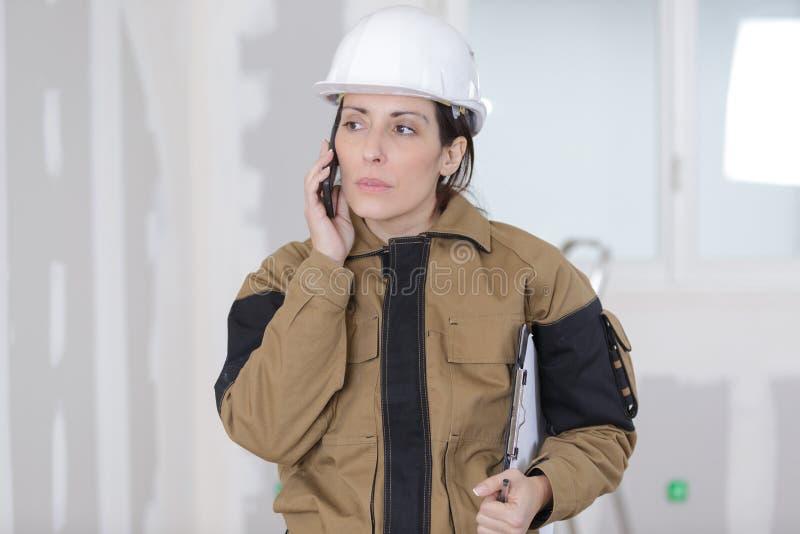 Żeński pracownik budowlany opowiada na telefonie na placu budowy zdjęcia royalty free