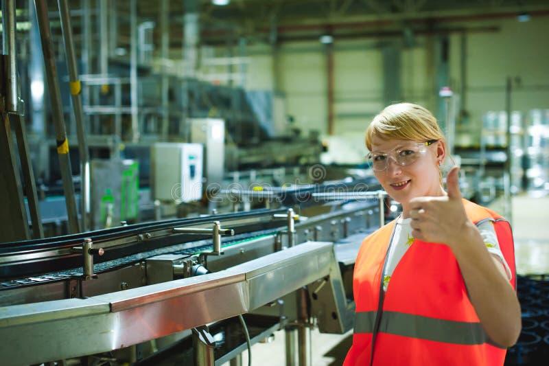 Żeński pracownik na piwnej fabryce portret kobieta w kontuszu, stoi na tło linii produkci żywności, Wizytacyjna zarządzanie kontr obrazy stock
