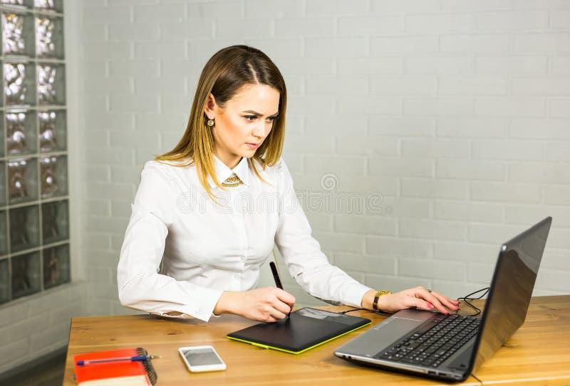Żeński projektant w biurowym działaniu z cyfrową graficzną pastylką i laptopem Fotografia retuszera obsiadanie przy biurkiem fotografia royalty free