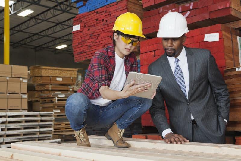 Żeński przemysłowy pracownik pokazuje coś na pastylka pececie męski inżynier zdjęcia stock