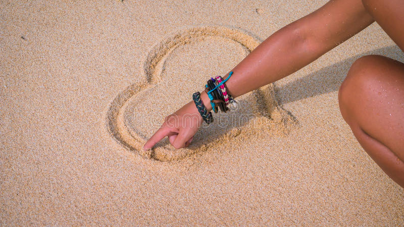 Żeński ręka remis na piasku blisko dennego serca fotografia stock