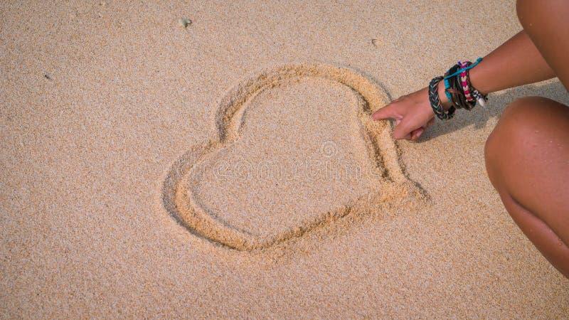 Żeński ręka remis na piasku blisko dennego serca zdjęcia royalty free