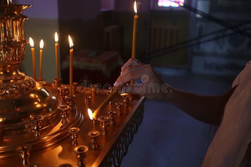 Żeński ręki zakończenie stawia kościół świeczka dla zdrowie obrazy stock