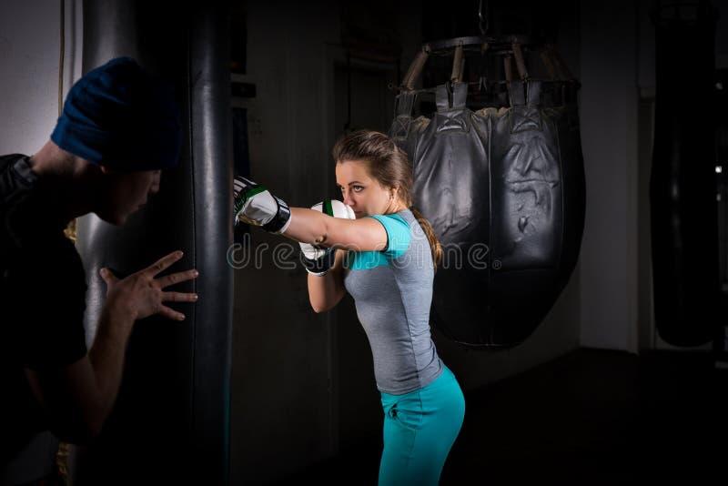 Żeński sporty bokser trenuje z jej leżanką w bokserskich rękawiczkach i fotografia stock