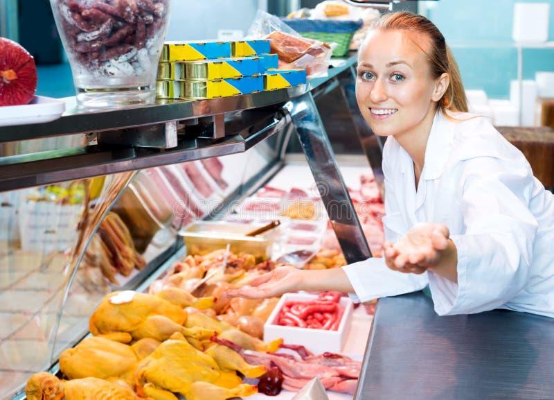 Żeński sprzedawca jest ubranym jednolitego działanie z świeżym mięsem obrazy stock