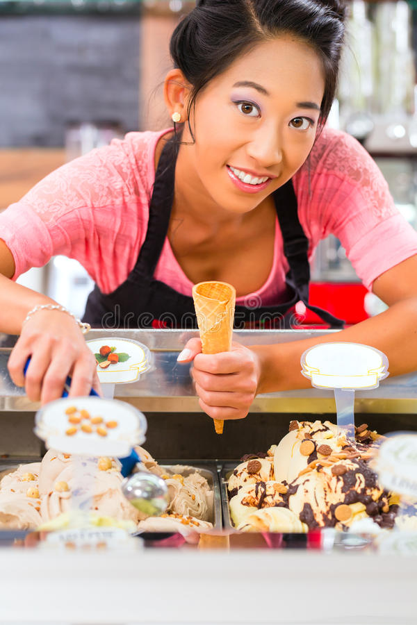 Żeński sprzedawca w bawialni z lody rożkiem obraz stock