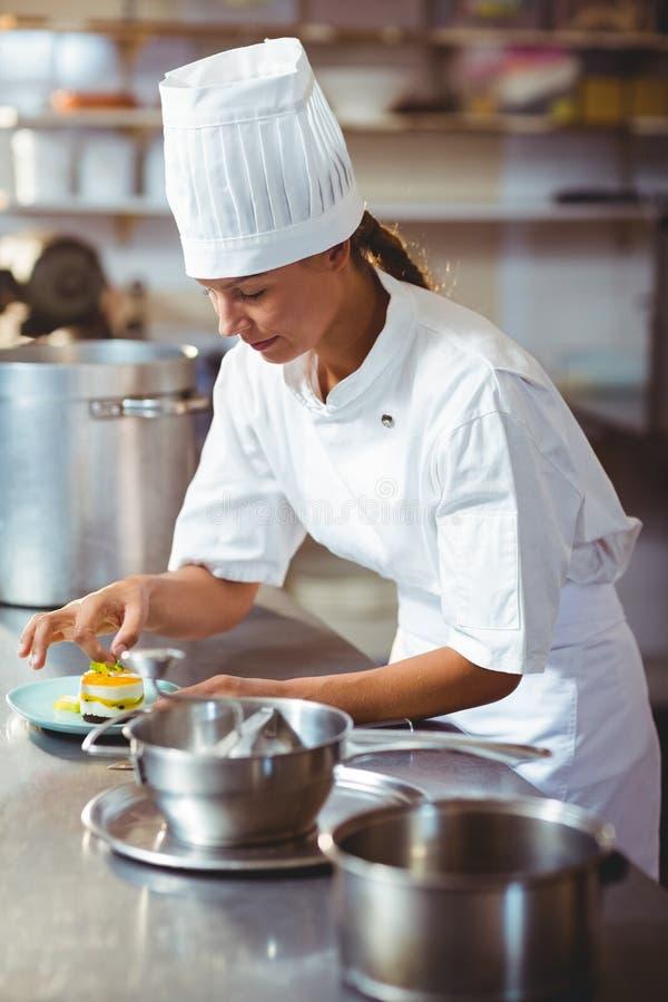 Żeński szef kuchni kończy deserowych talerze obrazy stock