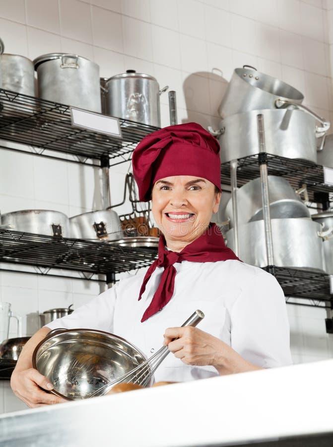 Żeński szef kuchni Miesza jajko Z Drucianym śmignięciem W pucharze obrazy stock