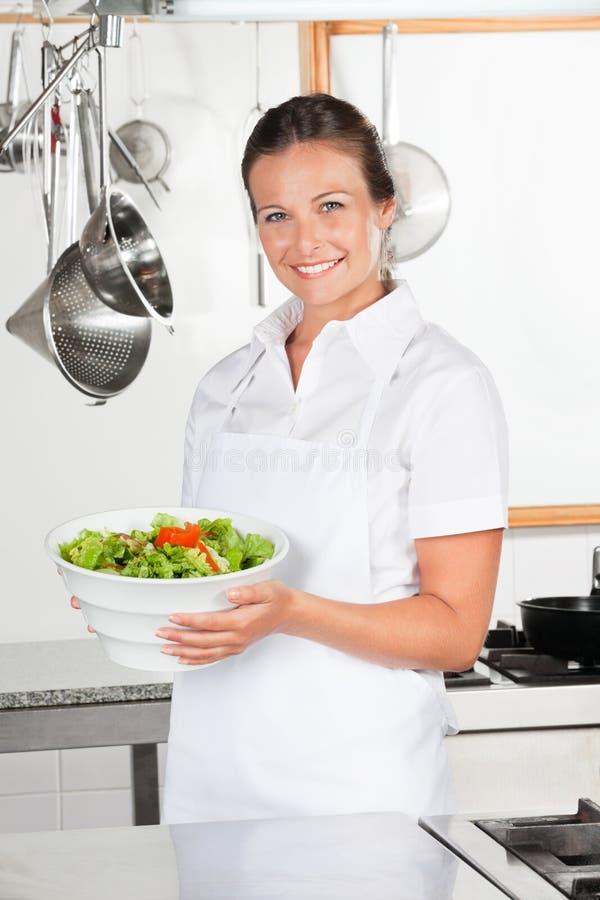 Żeński szefa kuchni mienia puchar sałatka obrazy stock