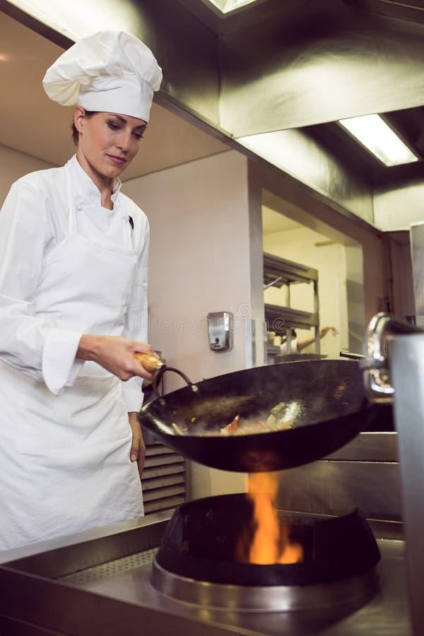 Żeński szefa kuchni narządzania jedzenie w kuchni obraz stock