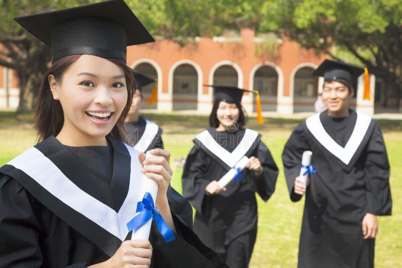 Żeński szkoła wyższa absolwent z kolega z klasy i trzymać dyplom obrazy stock