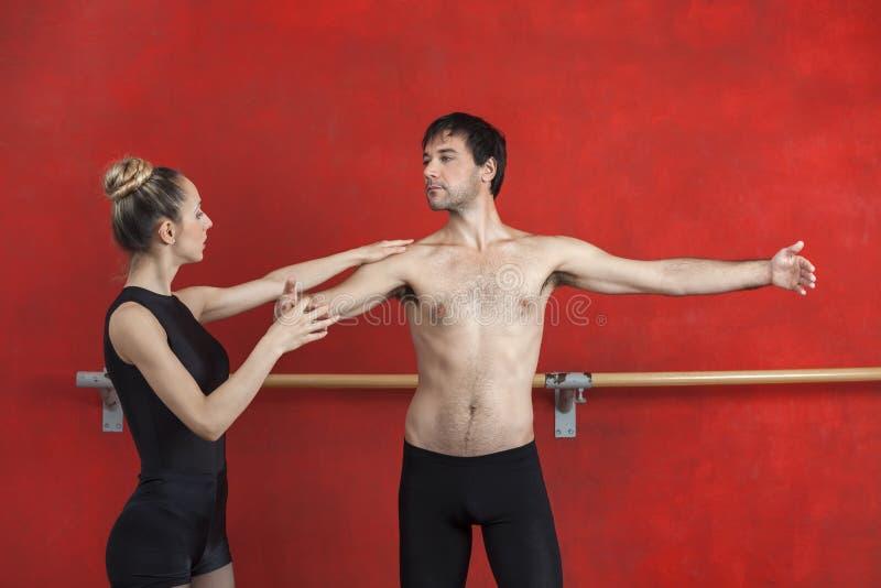 Żeński trener Pomaga Męskiego Baletniczego tancerza W studiu zdjęcie royalty free