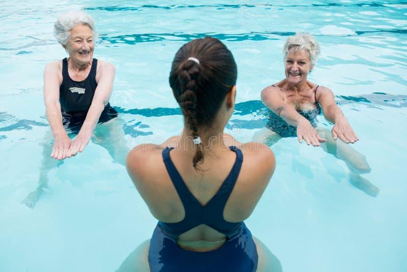 Żeński trener z starszymi kobietami ćwiczy w pływackim basenie obraz stock
