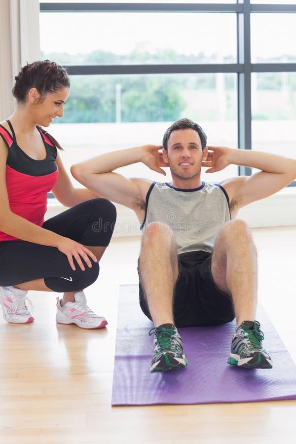Żeński trenera dopatrywania mężczyzna robi brzusznym chrupnięciom na ćwiczenie macie fotografia stock